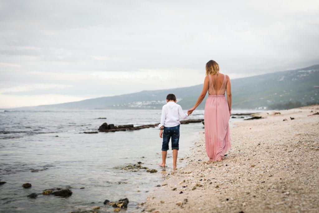 Une maman et son fils marchant sur la plage de Saint-Leu à l'île de la Réunion
