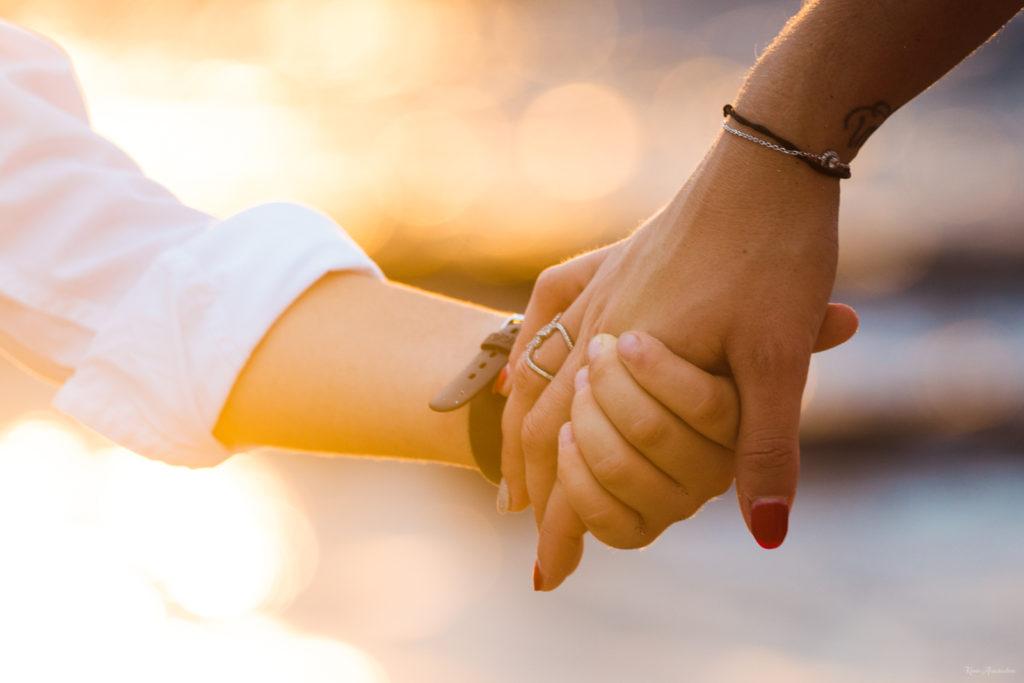 Photo main dans la main à la plage au coucher de soleil